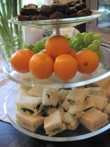 Sandwiches, fruit, and brownies on a fancy tiered platter.