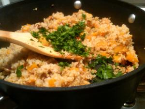 Toss the Accidental Butternut Bulgar with parsley and pecans to finish the dish.