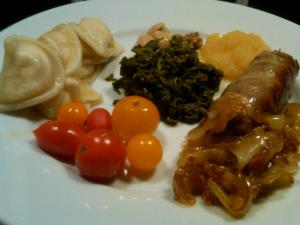 Caramelized onions over bratwurst with tomatoes, pierogies, and greens!
