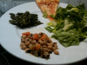 A traditional vegetarian New Year's meal: collard greens, black-eyed peas, salad, and cheese pizza.