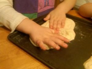 Press the pizza dough in the middle, pull out toward the sides.