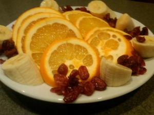 Sliced oranges (shown with dried cranberries and bananas) make a great side dish for garlicky pasta.