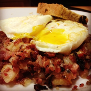 Corned beef hash with eggs over medium and Irish soda bread.