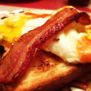 Fast Food: Toast, Egg Over Medium, Bacon, Sprinkle of Frank's Hot Sauce. Side of Watermelon.