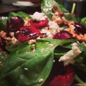 Spinach salad with walnuts, cherries, and goat cheese. Balsamic and olive oil drizzle. Fast Food.